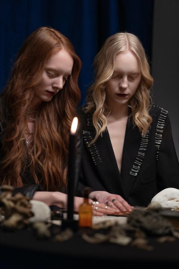 brujas pelirroja y rubia hablando con espiritus con tabla guija